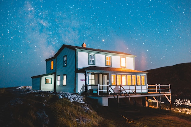 Biały i brązowy drewniany dom na wzgórzu pod błękitne niebo w porze nocnej