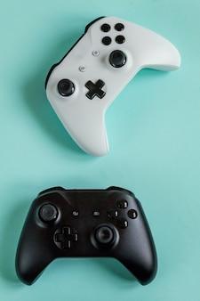 Biały i czarny dwa joystick gamepad, konsola do gier na pastelowej niebieskiej kolorowej modnej powierzchni. koncepcja konfrontacji kontroli gier komputerowych. symbol cyberprzestrzeni.