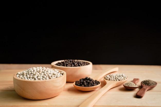 Biały i czarny pieprz w filiżance z tłem słojów drewna, koncepcja przemysłowa