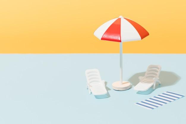 Biały i czerwony parasol plażowy leżaki i niebiesko-biały ręcznik w paski na niebieskim i żółtym tle plaża ustawiona na słoneczne dni koncepcja letnich wakacji kopiowanie miejsca