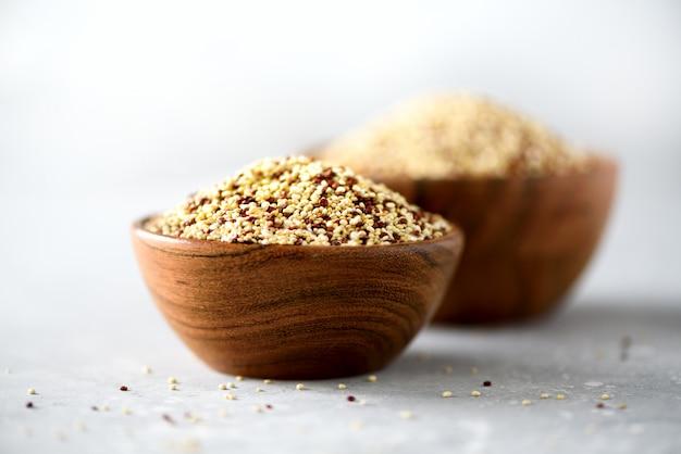 Biały i czerwony surowy organicznie quinoa w drewnianym pucharze i rozmarynach na szarym tle. zdrowe składniki żywności.