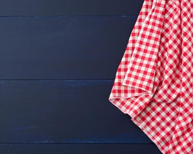 Biały i czerwony w kratkę ręcznik kuchenny na niebieskiej powierzchni drewnianej