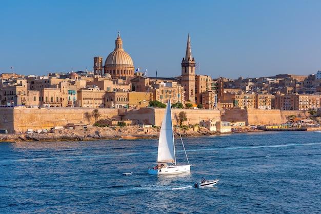 Biały jacht i stare miasto w valletcie z kościołami matki bożej z góry karmel i anglikańską prokatedrą św. pawła, valletta, stolica malty