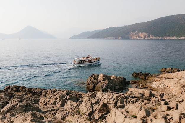 Biały jacht motorowy z turystami na pokładzie pływa wzdłuż skalistego wybrzeża na tle zieleni