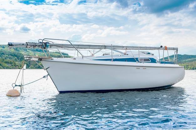 Biały jacht na jeziorze z niebieskim niebem.