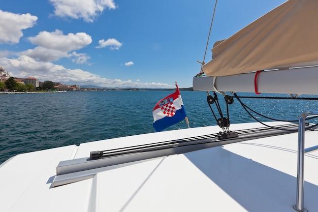 Biały jacht płynie po błękitnym morzu w chorwacji. strzał poziomy