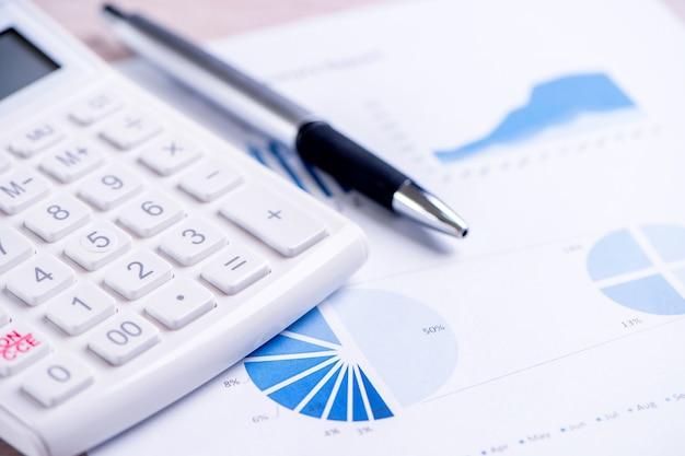 Biały kalkulator i raport z wykresem i wykresem, koncepcja rocznego przeglądu zysków finansowych, bankowości i inwestycji, miejsca kopiowania, makro, zbliżenie