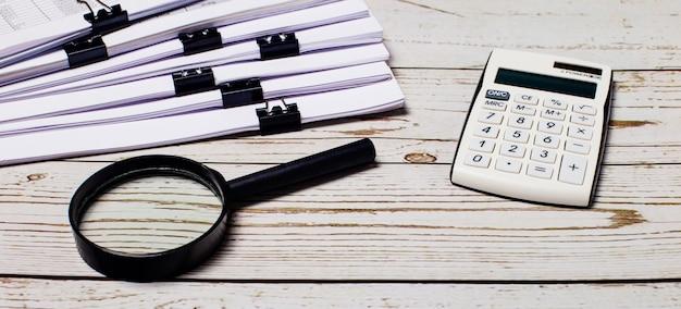 Biały kalkulator i szkło powiększające leżą obok stosu dokumentów na jasnej drewnianej powierzchni