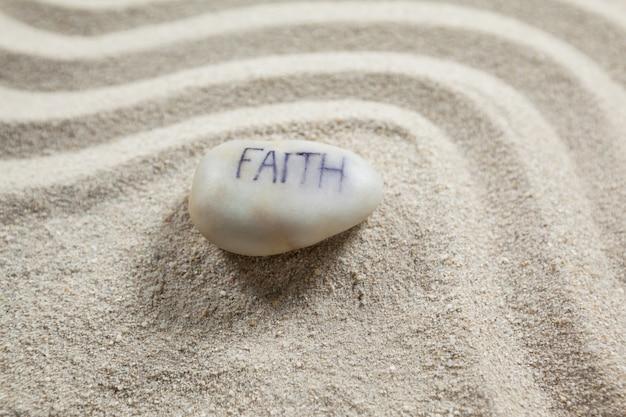 Biały kamyk z wygrawerowanym wiadomości wiary