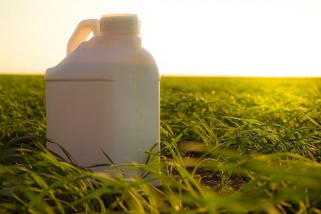 Biały kanister na tle kanistrów rolniczych spod różnych typów