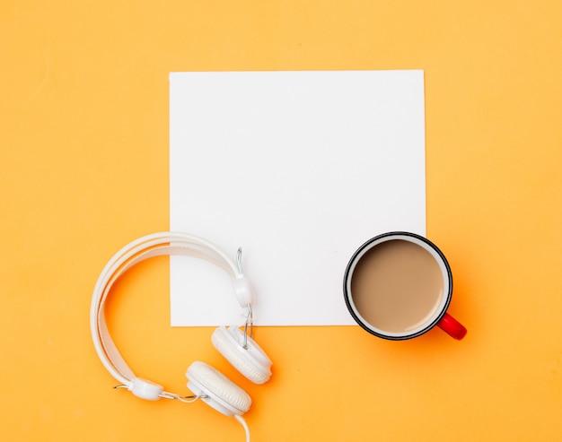 Biały karton i filiżanka kawy ze słuchawkami na żółto