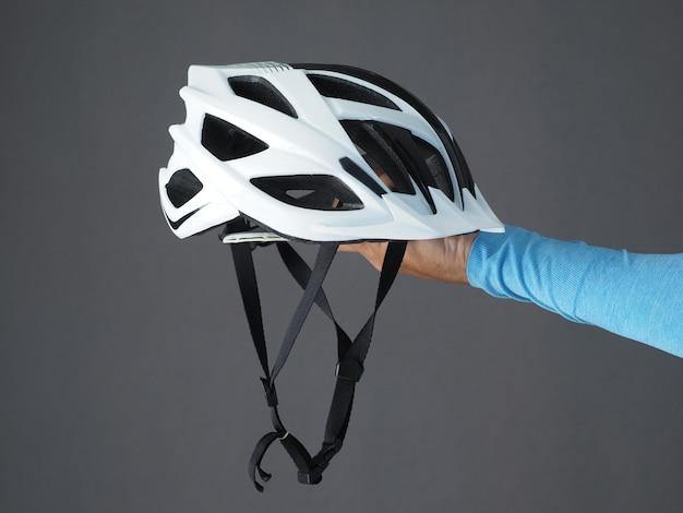 Biały kask rowerowy w dłoni. zbliżenie.