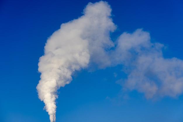 Biały, kłębiący się dym z komina na tle błękitnego nieba