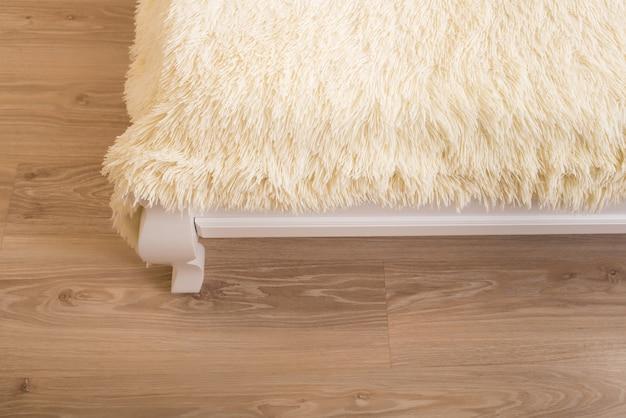 Biały koc ze sztucznego futra na łóżku w pokoju