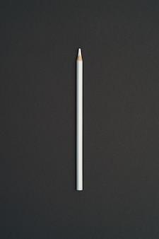 Biały kolorowy ołówek na białym tle na czarny stół