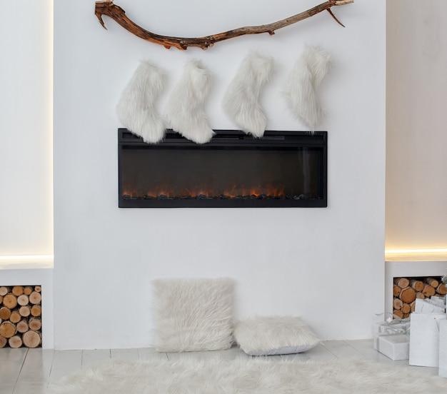 Biały kominek ozdobiony świątecznymi skarpetami