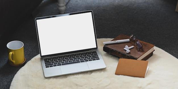 Biały komputer z pustym ekranem laptop wkłada na biały futrzany dywan w salonie