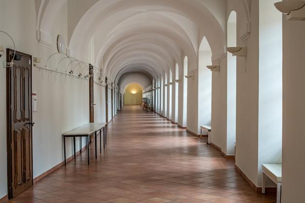Biały korytarz z wieloma drzwiami i światłami w budynkach użyteczności publicznej uniwersytet