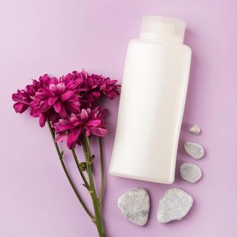 Biały kosmetyk produkt z menchiami kwitnie i zdrojów kamienie na różowym tle