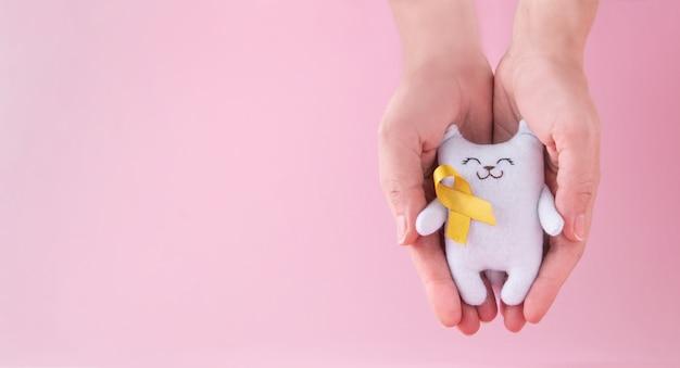 Biały kot w kobiecych dłoniach z żółtą wstążką świadomości raka dzieciństwa