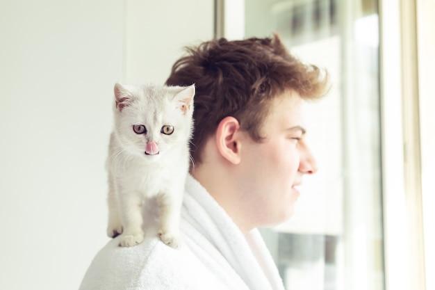 Biały kotek siedzący na ramieniu mężczyzny. wcześnie rano słońce. selektywne skupienie się na kocie.