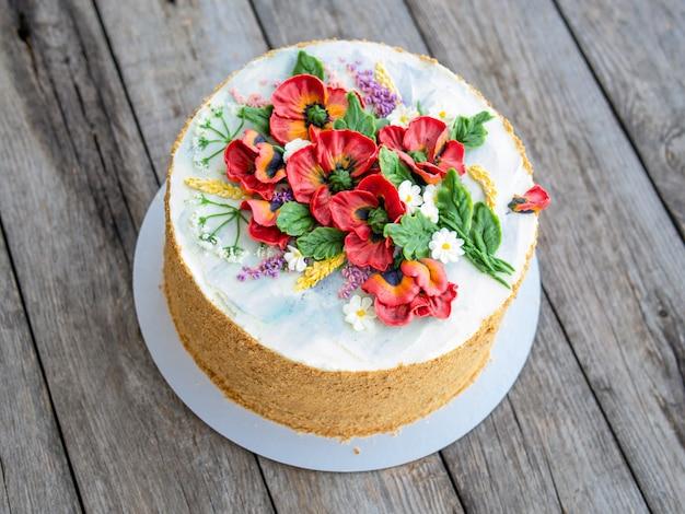 Biały kremowy tort ozdobiony kwiatami kremu