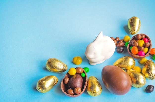 Biały króliczek wielkanocny z czekoladowymi jajkami owiniętymi złotą folią i cukierkami na jasnoniebieskim