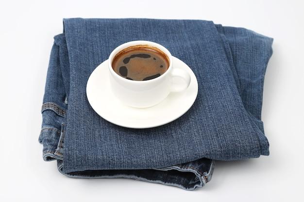 Biały kubek czarnej kawy spoczywa na dżinsowych spodniach