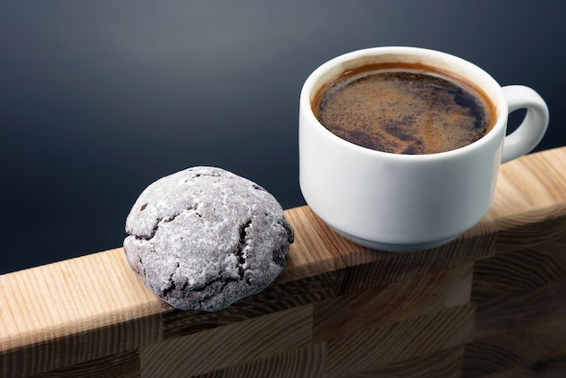 Biały kubek czarnej kawy z ciasteczkami na drewnianych