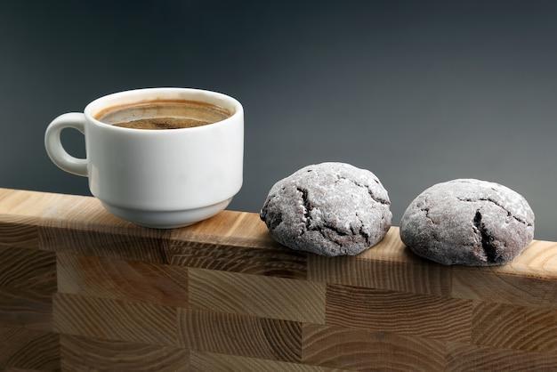 Biały kubek czarnej kawy z ciastkami na drewnianej ramie