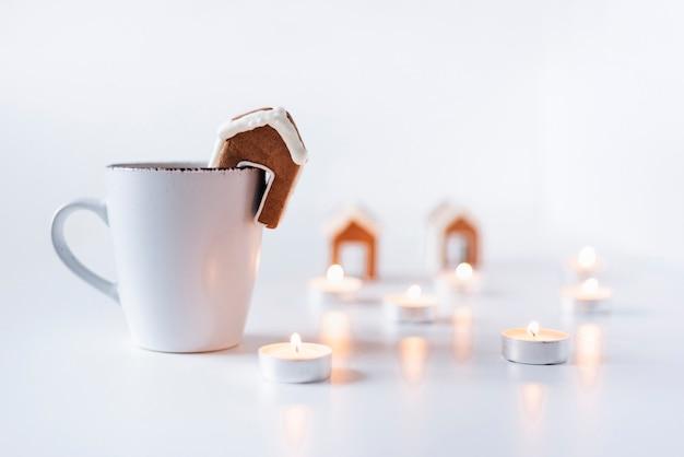 Biały kubek, domek z piernika i świeczki. przerwa świąteczna.