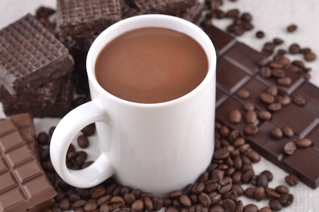 Biały kubek gorącej czekolady na ziarnach kawy i czekoladowym tle