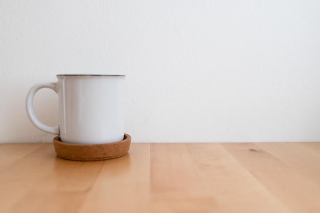 Biały kubek gorącej kawy na drewnianym stole i białej ścianie z miejsca na kopię.