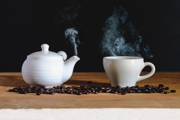 Biały kubek gorącej kawy z białym garnkiem i fasolą palącą na stole.