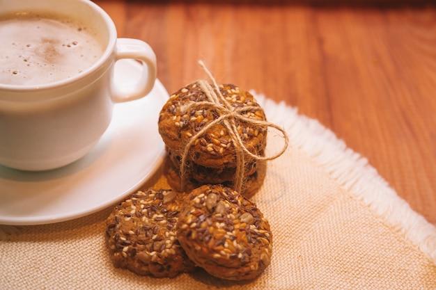 Biały kubek gorącej kawy z ciasteczkami na talerzu na ciemnym drewnianym stole
