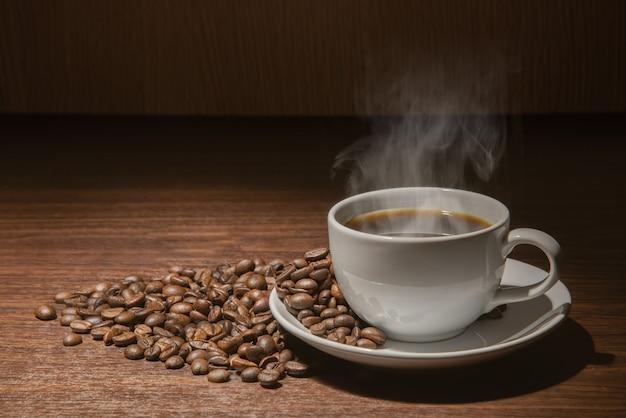 Biały kubek gorącej kawy z dymem z ziaren kawy i wór pełen ziaren kawy ze sznurem
