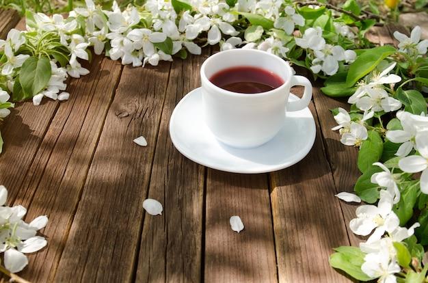 Biały kubek herbaty na drewnianym stole, w tle kwiaty jabłoni. słoneczny widok z boku