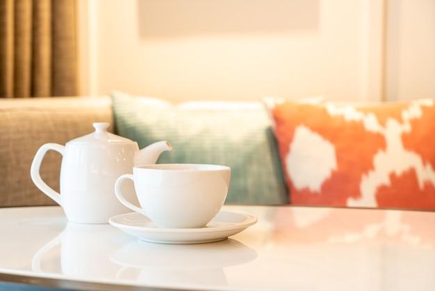 Biały kubek herbaty z imbryk na stole