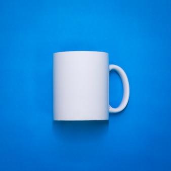 Biały kubek kawy na niebieskim tle papieru