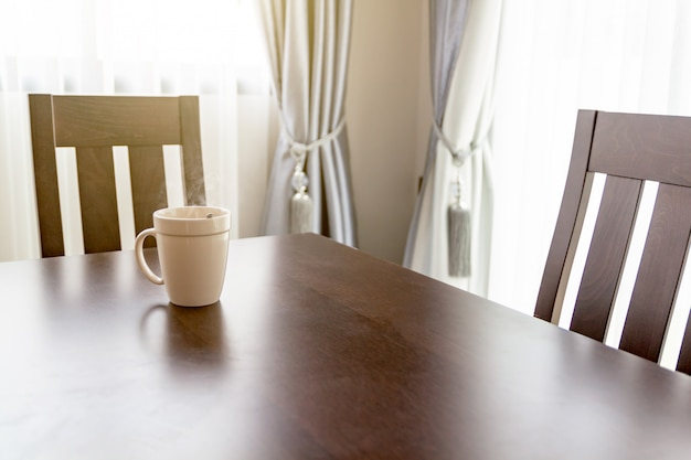Biały kubek kawy umieszczony na drewnianym biurku rano.