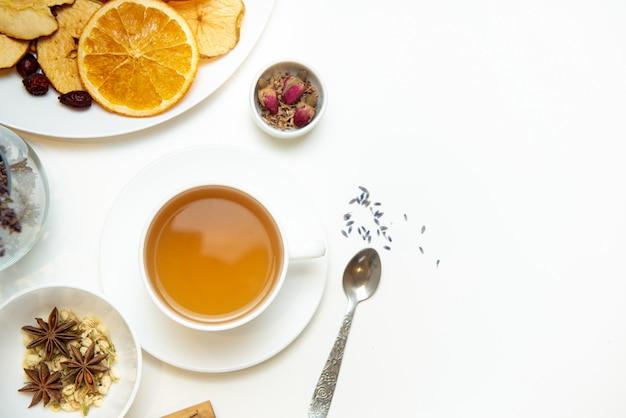 Biały kubek na białym stole z rozłożoną na stole herbatą ziołową i składnikami ziołowymi. koncepcja na temat leczenia ziołami przeziębienia i grypy jesienią. widok z góry