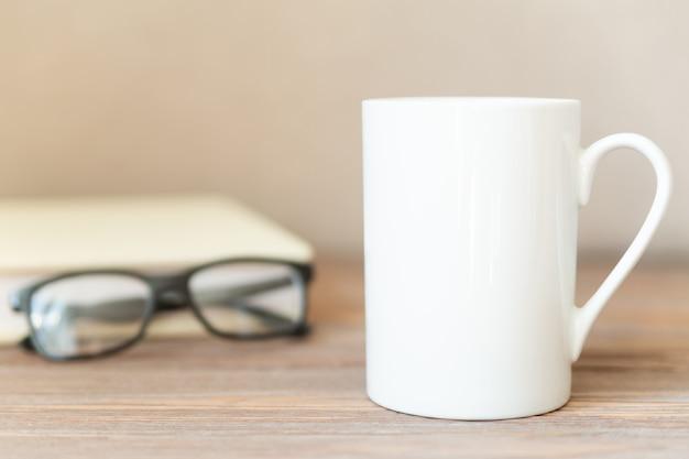 Biały kubek na drewnianym stole z notatnikiem i okularami.