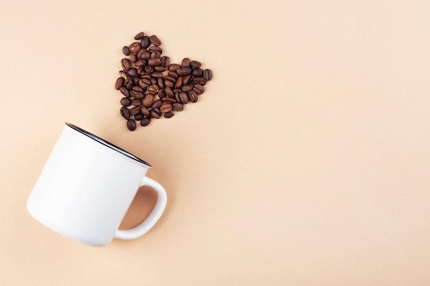 Biały kubek na stole, widok z góry, ziarna kawy w kształcie serca