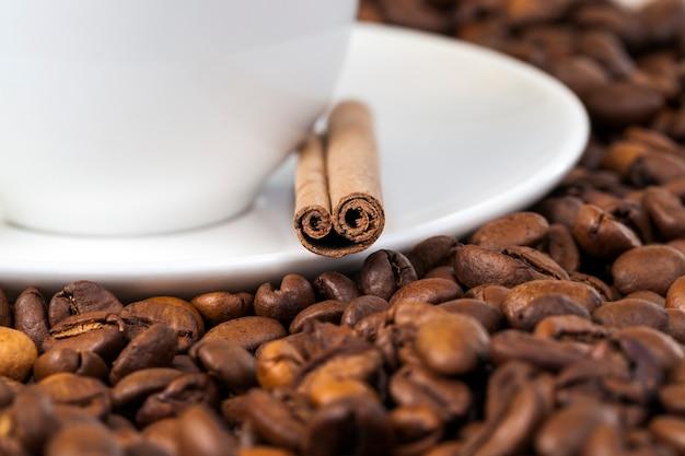Biały kubek na stosie ziaren kawy, na talerzu leżą całe laski cynamonu