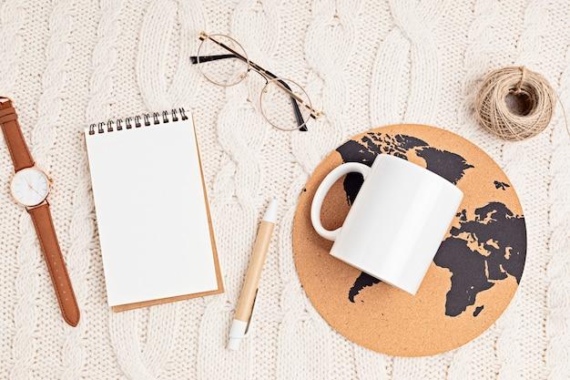 Biały kubek, okulary, zegarek, długopis, notatnik i nadruk na świecie. stylowe akcesoria do biura lub podróży. widok płaski, widok z góry