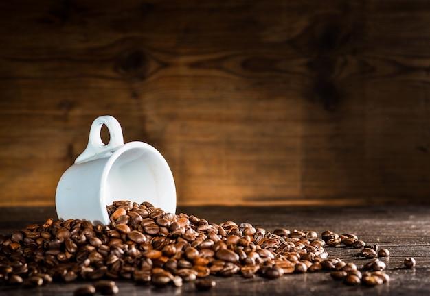 Biały kubek otoczony ziaren kawy