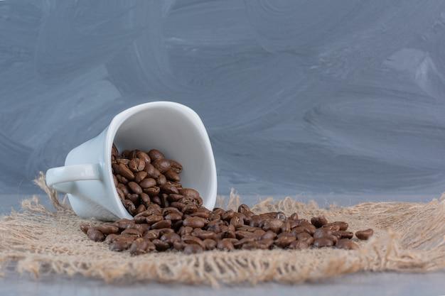 Biały kubek palonych ziaren kawy na marmurowym tle.