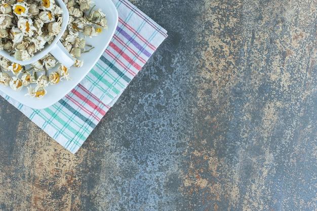 Biały kubek pełen suszonego rumianku na obrusie.