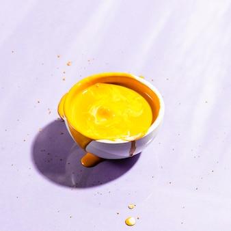 Biały kubek pod wysokim kątem z żółtą farbą