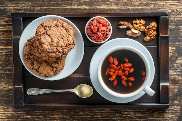 Biały kubek świeżej porannej kawy goji z ciasteczkami na drewnianej tacy na stole, widok z góry, z bliska. czarna gorąca kawa z całymi czerwonymi jagodami goji